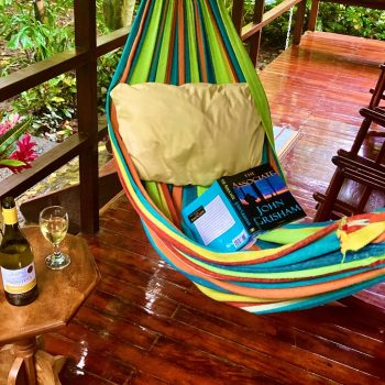 Inviting colorful hammock on spacious porch with open book and glass of wine